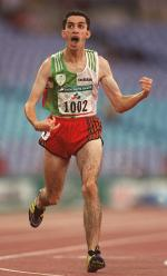 Man in running clothes, crossing a finish line, celebrating