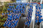 Group picture of many people in blue shirts, shot from above