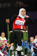 Women with headscarf doing shot put (sitting)