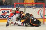 Two ice sledge hockey players fighting for the puck.
