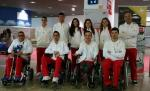 Group shot of athletes standing and in wheelchairs at an airport.