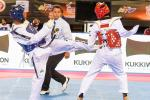 A taekwondo athlete kicks another taekwondo athlete