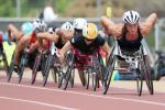 A wheelchair racer leads a line of competitors on a red track.