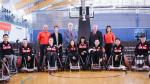 Twelve athletes in wheelchairs lined up, making up the wheelchair rugby team.