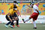 Three blind athletes playing football on a field at the Parapan American Games
