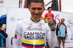 Man with cycling jersey showing his medal, smiling