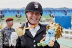 A dressage rider celebrating her medal.