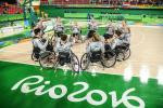 Women in wheelchairs forming a circle on a basketball field