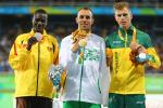 Uganda's track and field athlete David Emong celebrates on the podium with the gold and bronze medallists.
