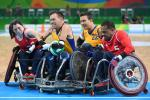 Four wheelchair rugby players fighting for the ball.