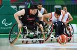 Two men in wheelchairs chasing a basketball