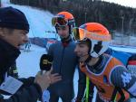 A visually impaired skier and his guide are interviewed