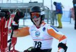 Man in ski helmet and goggles smiles in a sit ski