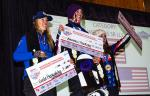 Three women on the podium, holding big checks
