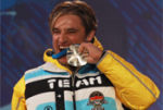 A picture of a man beating his silver medal during a medal ceremony