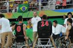 Coach surrounded by his men's wheelchair basketball team giving instuctions