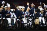 South Korean athletes in wheelchairs hold flags as they enter the stadium
