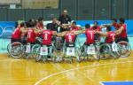 Men in basketball wheelchairs huddle around each other