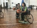Woman in wheelchair shooting a basketball