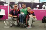 Man in wheelchair between two people posing for photo