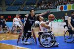 Man in wheelchair tries to block another man in wheelchair playing basketball