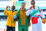 three men stand on a podium with their medals