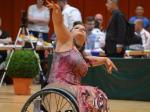 a para dancer in a wheelchair raises her arms