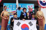 three South Korean shooters with their medals and their flag