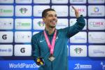 a male Para swimmer celebrates on the podium