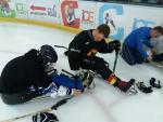 Two men in Para ice hockey sledges, one helping another get in the sledge