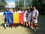 Seven men, some of them blindfolded hold a Romanian flag, celebrate.