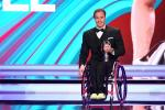 Man in wheelchair dressed in a suit holding a trophy