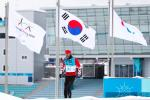a male Para Nordic skier walks past the Paralympic and South Korean flags