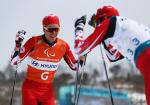 a male Para Nordic skier celebrates with his guide
