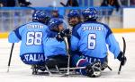 a group of Para ice hockey players celebrate on the ice