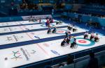 a wide shot of four wheelchair curling matches underway