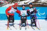 three female sit skiers celebrate their medals