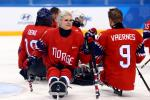 a female Para ice hockey player with her teammates on the ice