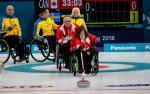 a female wheelchair curler plays a stone