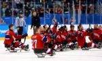 a group of Para ice hockey players celebrating on the ice