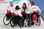 four wheelchair curlers gather in a huddle
