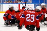 a group of Para ice hockey players celebrate a goal