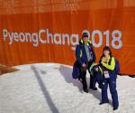 Two winter sport officials pose in front of a PyeongChang 2018 banner