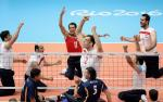 Group of sitting volleyball players celebrate after a point.