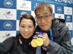 a man and a woman hold up a medal
