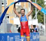 a male Para triathlete holds up the finish line tape as he crosses