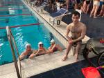 Three swimmers in the pool and one swimmer out of the pool posing for a picture
