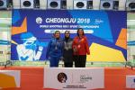 Three female shooting athletes pose on the podium