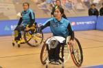 Woman badminton player in wheelchair hits a birdie