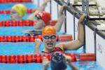 a female Para swimmer punches in the air in the pool